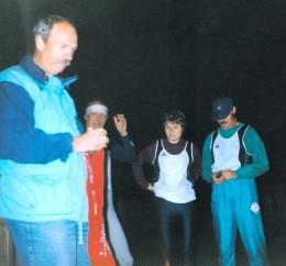 """Start 4 Uhr in der Nacht an der Selbitz in Blankenstein 1995. Dr. Rolf Schoder, Dr. Peter Fuchs und Heidrun Garlipp (v. l.) vom USV Jena. Rolf Schoder hält das """"Rote Band"""" in den Händen, welches die Staffelläufer übergeben mussten. In einer kleinen Tasche war nach Rennsteigtradition ein kleiner Stein von der Selbitz, der am Ende des Rennsteigs in Hörschel in die Werra geworfen wurde."""