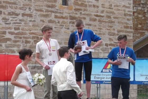 Das Brautpaar Michael und Stefanie Teichmann führen gemeinsam mit Sömmerdas Bürgermeister Ralf Hauboldt  die Siegerehrung im 4-Kilometer-Lauf durch.