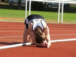 Peter Rodewald erschöpft auf dem Tartan, nachdem er seinen Stadionrekord gebrochen hat
